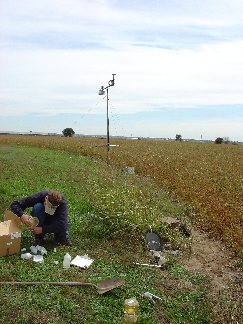 Photo showing man collecting water sample at monitoring site adjacent to bean field.